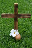 foto of crucifiction  - Wooden cross depicting crucifix upright on grass with symbolic egg and flower - JPG