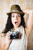 stock photo of jaw drop  - Surprised hipster woman taking photos with retro film camera on vintage ornamental wallpaper - JPG