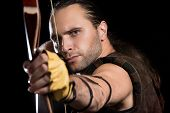 stock photo of longbow  - Young man has some dangerous hobby - JPG