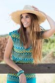Portrait Of A Happy Girl Wearing Straw Hat Looking Away