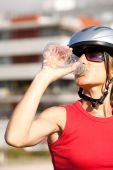 stock photo of drinking water  - young woman drinking water after doing some bicycle exercise - JPG