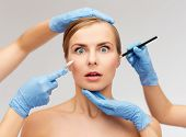 healthcare, beauty and medicine concept - beautiful woman face and beautician hands with pencil and