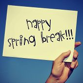 image of spring break  - a man hand holding a signboard with the text happy spring break written in it - JPG