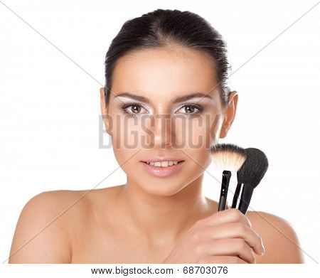 Portrait of attractive young adult woman applying blusher
