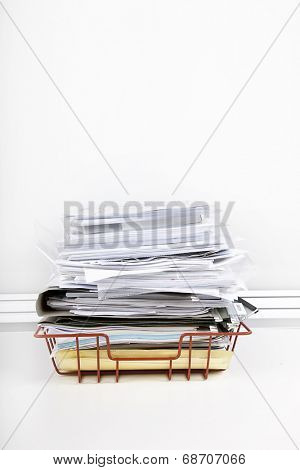 Documents overflowing in desk tray against white wall