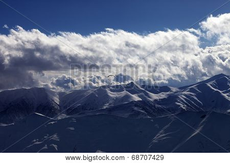 Evening Sunlight Mountain With Clouds And Silhouette Of Parachutist