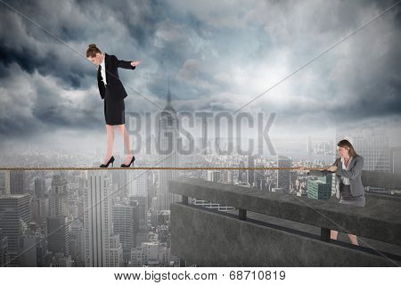 Young business woman pulling a tightrope for businesswoman against balcony overlooking city