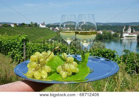 Pair of wineglasses against Rhine river and vineyards in Rheinau, Switzerland