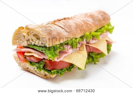 Long Baguette Sandwich with Lettuce, Tomatoes, Ham and Cheese cut in half
