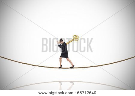 Wound up businesswoman gesturing on tightrope against white background with vignette
