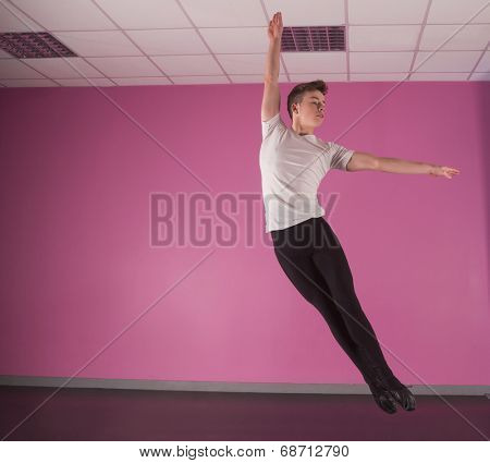 Focused male ballet dancer leaping up in the dance studio