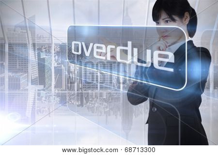 Businesswoman looking at the word overdue against room with large window looking on city