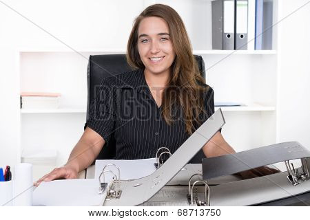 Young Woman Is Sitting In Front Of A Pile Of Files