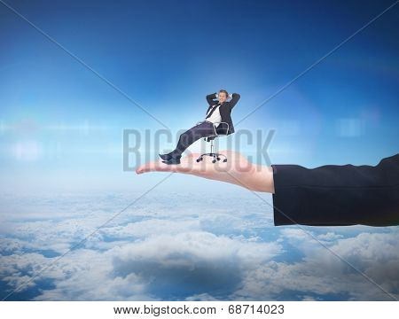 Businessman relaxing in swivel chair against blue sky over clouds at high altitude