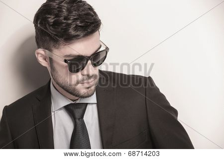 side closeup picture of a sexy young business man wearing sunglasses and looking away