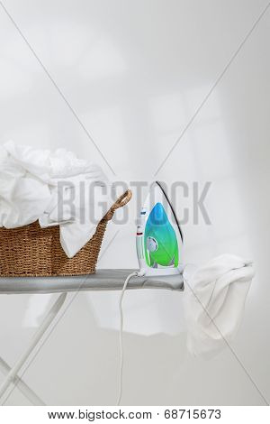Basket of freshly laundered washing and electric iron on board