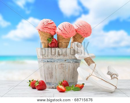 Strawberry fruit ice creams with nautical anchor and beach blur background