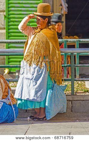 LA PAZ, BOLIVIA, MAY 8, 2014 - Local woman in traditional costume and bowler hat waits near San Francisco church