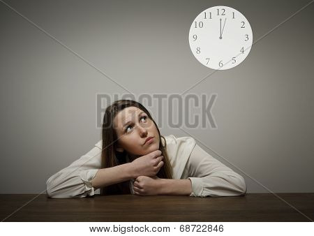 Girl In White And A Clock Showing Several Minutes Past Twelve.