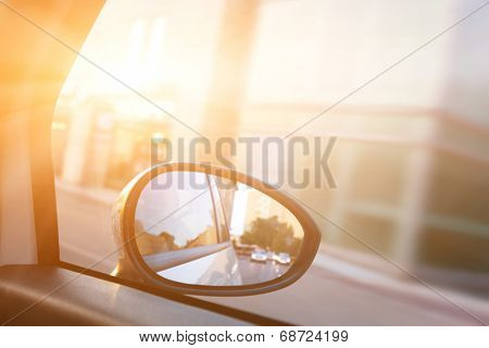 Dynamic view from car on the wing mirror during drive. Sun shining. Transportation, travel, speed.
