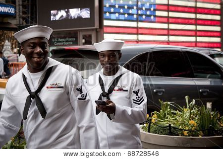 NEW YORK - MAY 23: Two US Navy sailors on liberty pass the lighted US Flag on the Armed Forces Recruiting Center in Times Square during Fleet Week NY.