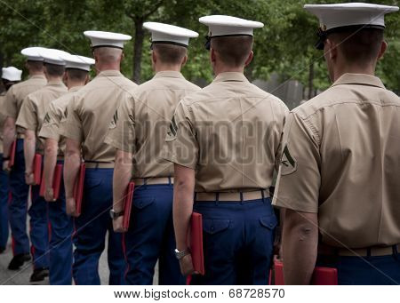 NEW YORK - MAY 23, 2014: A group of U.S. Marines exit in a single file line after taking part in the re-enlistment and promotion ceremony at the National September 11 Memorial site.