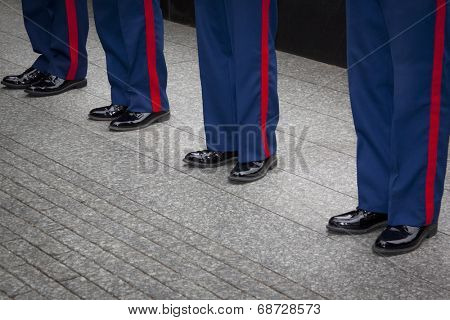 NEW YORK - MAY 23, 2014: Blue trousers with the scarlet blood stripe of four U.S. Marines Corpsmen participating in the re-enlistment and promotion ceremony at the National September 11 Memorial site.