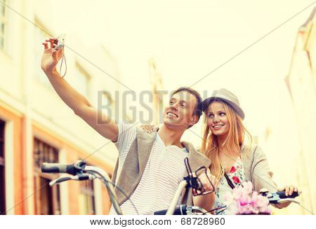 summer holidays, travel, vacation, tourism and dating concept - travelling couple with bicycles taking photo picture with camera