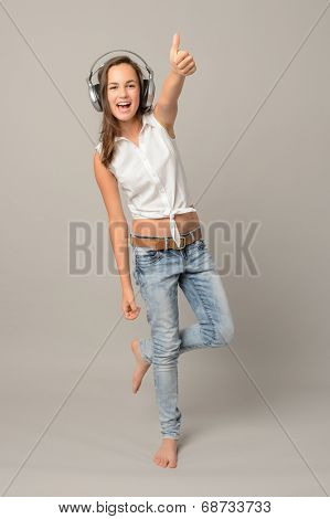 Girl enjoy listening music and dance thumb-up full length on gray