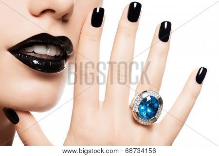 Macro shot of a woman's lips and nails painted bright color black. Person holds in mouth blue stone.