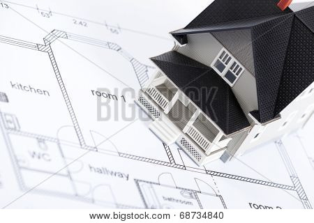 Realty concept - construction plan with  household architectural model on it