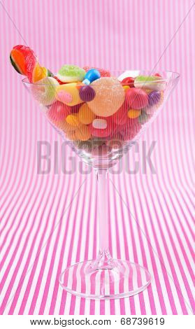 Different colorful fruit candy in glass on pink background