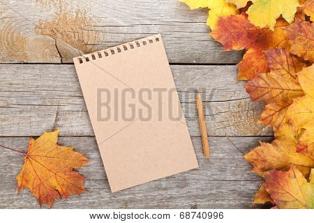Blank page and colorful autumn maple leaves on wooden table background