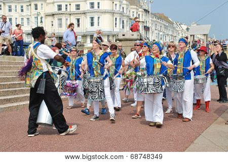 ST.LEONARDS-ON-SEA, ENGLAND - JUNE 12, 2014: Dende Nation, Samba drum troupe, perform during a parade on the seafront at the annual St.Leonards Festival. The community event was first held in 2006.
