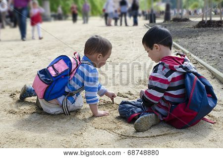 Children Drawing Into Sand With Stick