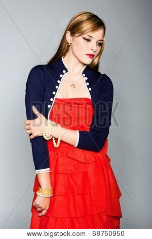 Portrait of a young woman in red dress and navy blue jacket. Wearing long hair loose and antique gold and pearl jewelery over grey studio background