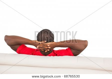 Man in red jersey sitting on couch on white background