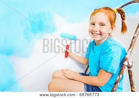 Little girl in blue shirt sits on a ladder