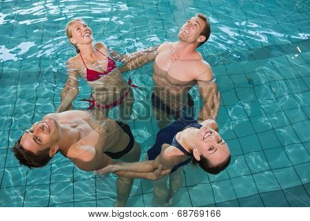 Happy fitness class stretching in aqua aerobics in swimming pool at the leisure centre