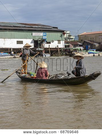 Woman Ferries Two Other Women In Her Small Rowboat.