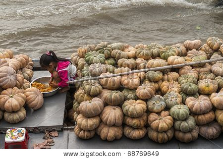 Sitting Among A Pile Of Pumpkins On Her Parents Barge.