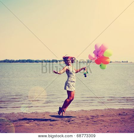 a pretty woman enjoying summer outside with a bunch of balloons toned with a retro vintage instagram filter