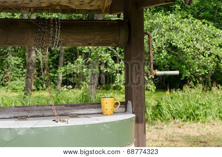 Edge Of Old Well Pulley With Chain And Mottled Cup