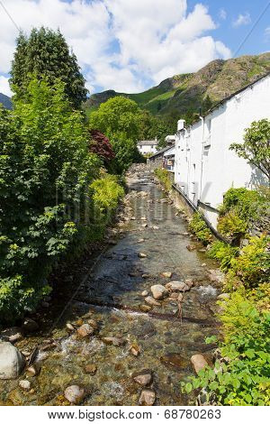 View of stream and mountains in Coniston town Lake District England with hot sunny summer weather