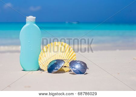 Bottle of suncream, sunglasses and shell on the white beach