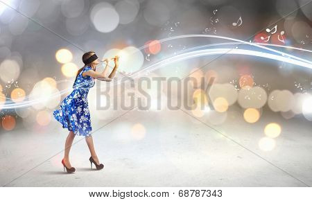 Young woman in blue dress wearing blindfold and playing fife