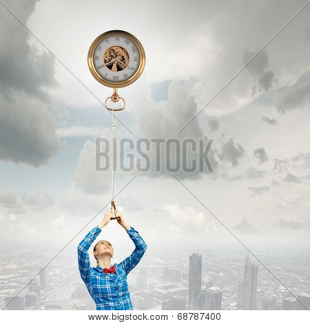 Young woman standing on edge of rock with pocket watch