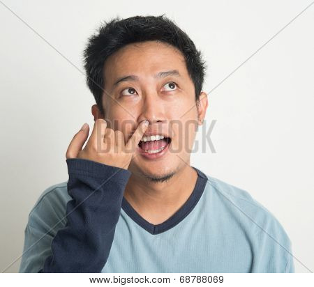 Disgusting Asian man picking nose with eyes looking up, on plain background