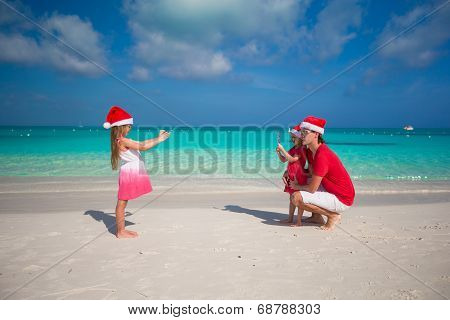Cute girl making photo on phone father and sister at the beach
