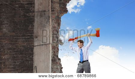 Young determined businessman crashing wall with axe